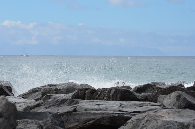 Rock;sky;ocean;splashes royalty free stock images