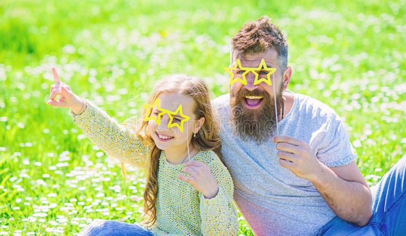 Rock star concept. Dad and daughter sits on grass at grassplot, green background. Family spend leisure outdoors. Child. And father posing with star shaped stock photo