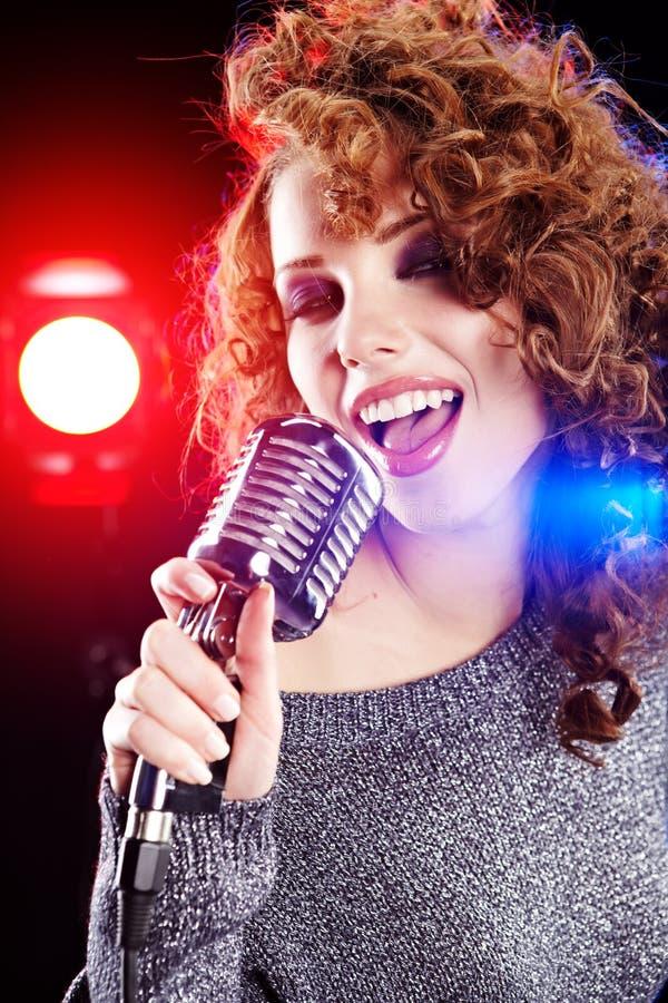 Rock star. Donna che canta nel retro mic fotografia stock libera da diritti