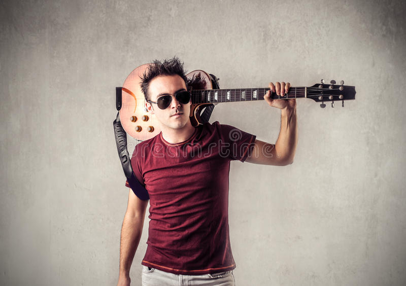 Rock star. Man acting like a rock star with a guitar stock photo