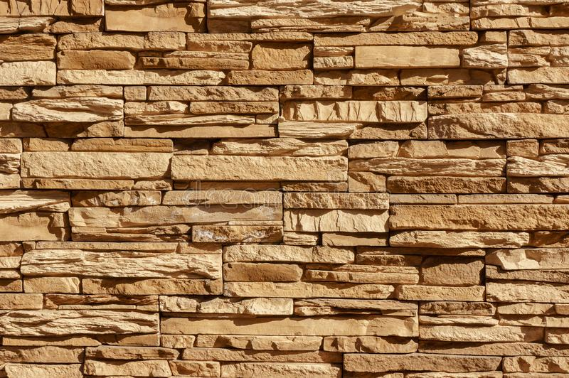 Rock stone brick tile wall has a detailed background texture sepia cream brown color stacked in layers, you can use this royalty free stock photography