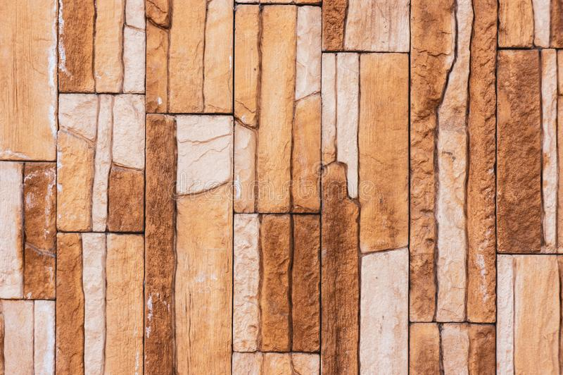 Rock stone brick tile wall has a detailed background texture sepia cream brown color stacked in layers, you can use this royalty free stock image