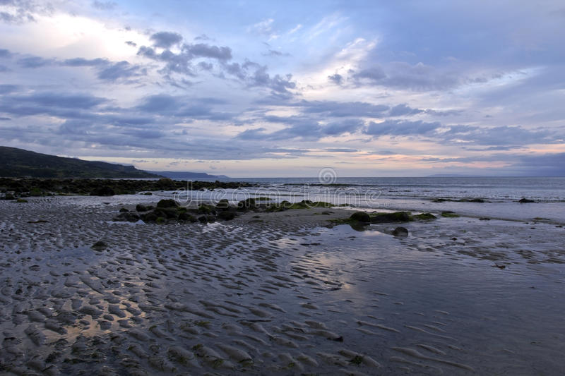 The Rock Strewn Ballygally Beach and Ballygally Bay, beautiful in early morning light royalty free stock images