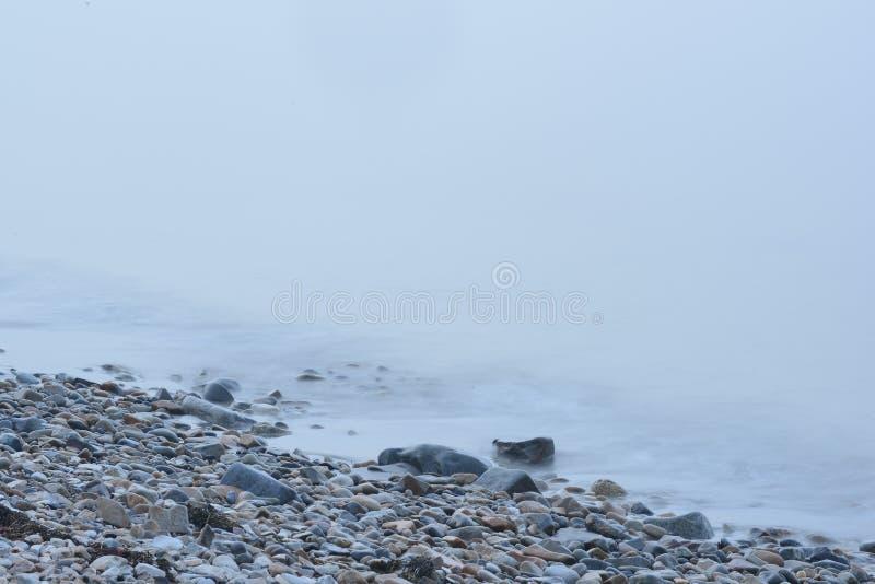 Rock strewn Coastal Maine Beach in heavy fog