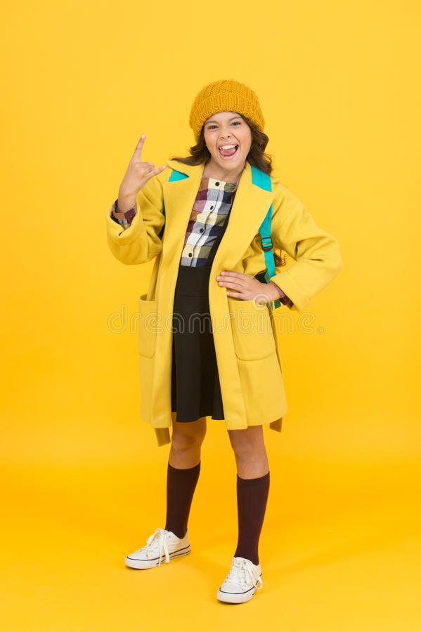 In rock style. Small girl gesture horn sign in formal style. Little cute child wear autumn fashion style. School dress. Code. School uniform never goes out of stock photography