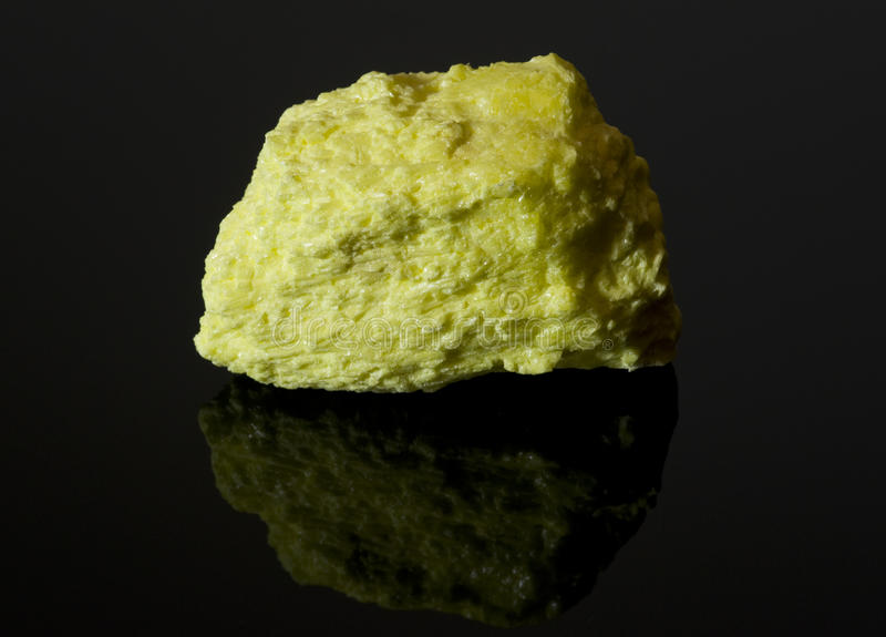 Rock of sulfur on black reflective surface stock photography