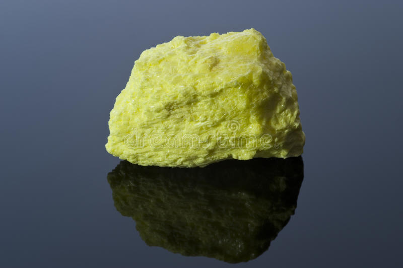 Rock of sulfur on black reflective surface royalty free stock photo