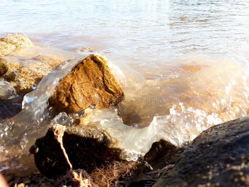 Rock surf. Water surfs around brown stone. Sea surf stock photography