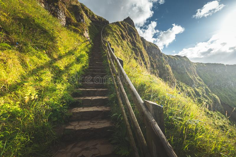 Rock up stairs with wooden railing. Irish land. Rock stairs with wooden railing. Northern Ireland landscape. The stone path over the precipice. The touristic stock photography