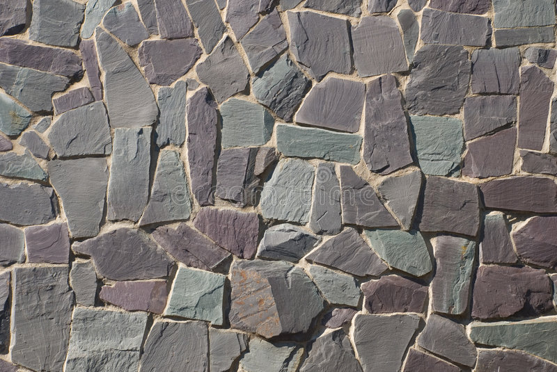 Rock wall or path. A thick textured slate or shale rock wall or path in a crazy random pattern royalty free stock photo