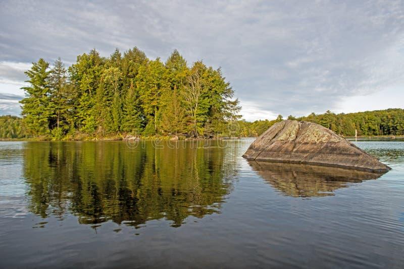 Rock wijst weg van een klein, bebost eiland royalty-vrije stock afbeelding