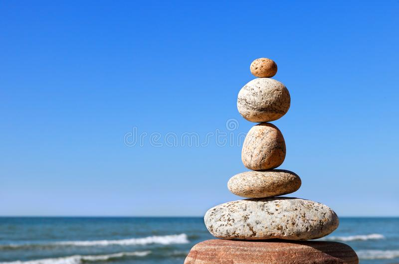 Rock zen pyramid of gray pebbles on a background of blue sky and sea.  stock images