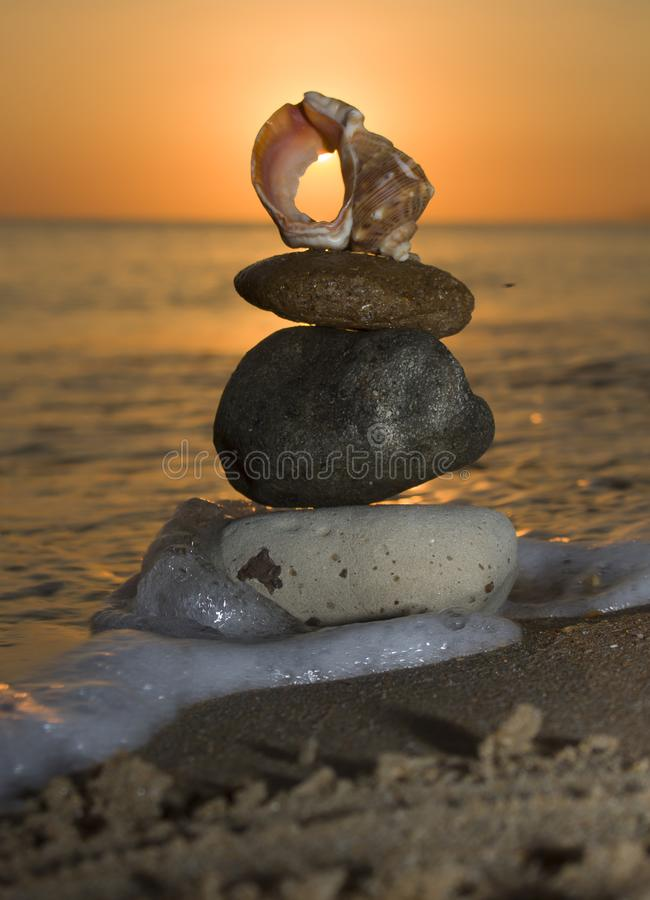 Rock zen pyramid of yellow stones on a background of blue sky and sea. Concept of balance, harmony and meditation royalty free stock photography