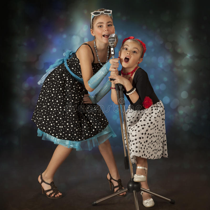 Rockabilly girls posing with vintage microphone stock photos