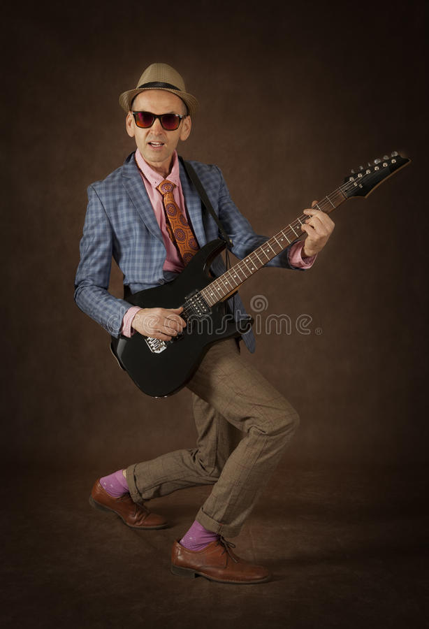 Rockabilly man playing the guitar stock images