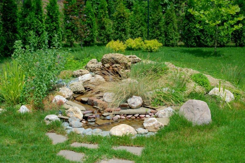 Rockary sob a forma de uma cachoeira da montanha no jardim com pedras e muitas flores e plantas diferentes fotos de stock royalty free