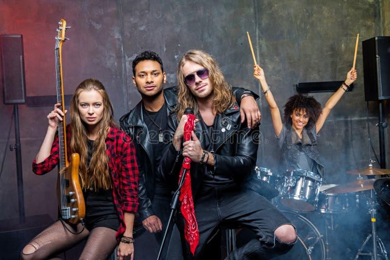 Rockband som poserar i studio fotografering för bildbyråer
