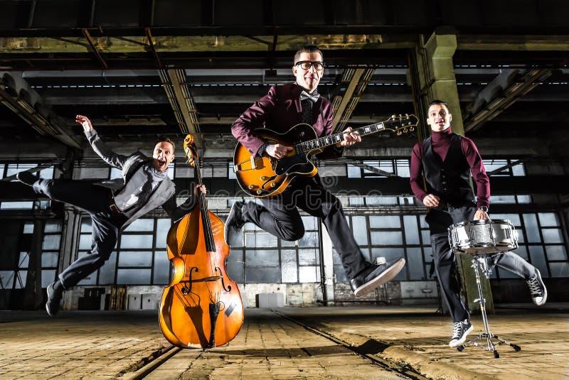 Rockbandet hoppar in i luften i en industribyggnad royaltyfri fotografi