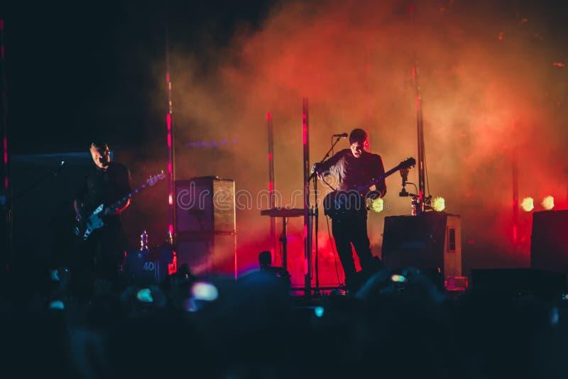 Rockbandet utför på etapp Gitarristen spelar solo Kontur av gitarrspelaren i handling på etapp framme av konsertfolkmassan royaltyfria foton