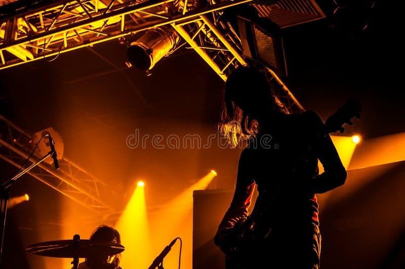 Rockbandet utför på etapp Gitarristen spelar solo Kontur av gitarrspelaren i handling på etapp framme av konsertfolkmassan arkivfoto