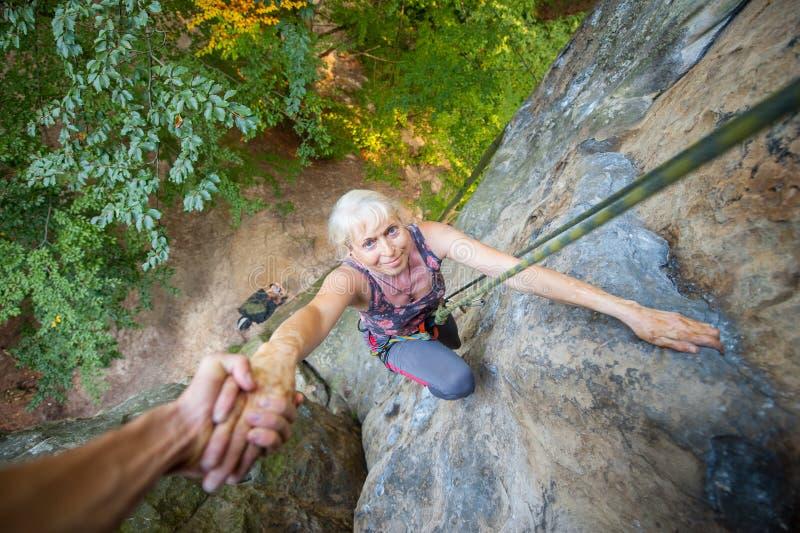Rockclimber que ajuda ao montanhista fêmea a alcançar a parte superior da montanha fotografia de stock royalty free