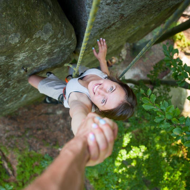 Rockclimber que ayuda al escalador femenino a alcanzar el top de la montaña fotos de archivo libres de regalías