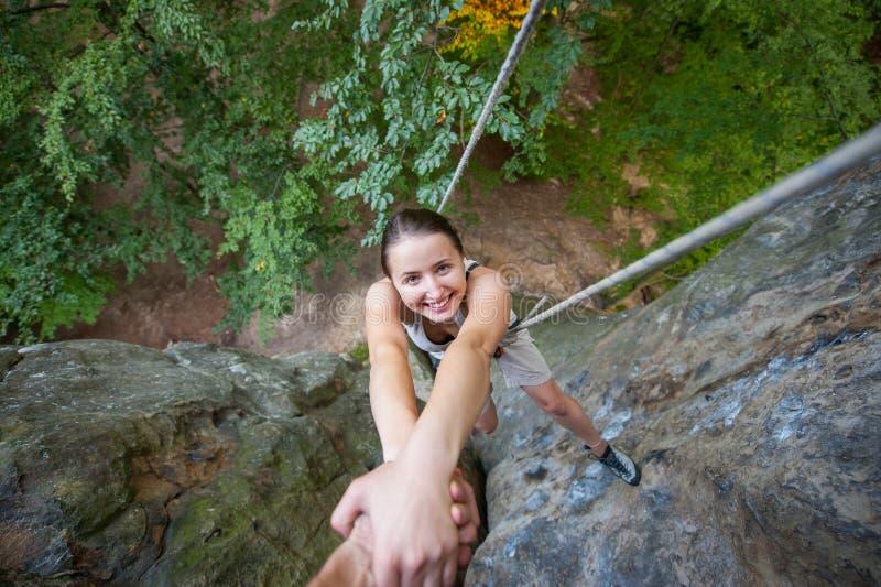 Rockclimber som hjälper till den kvinnliga klättraren att nå överkanten av berget royaltyfria bilder