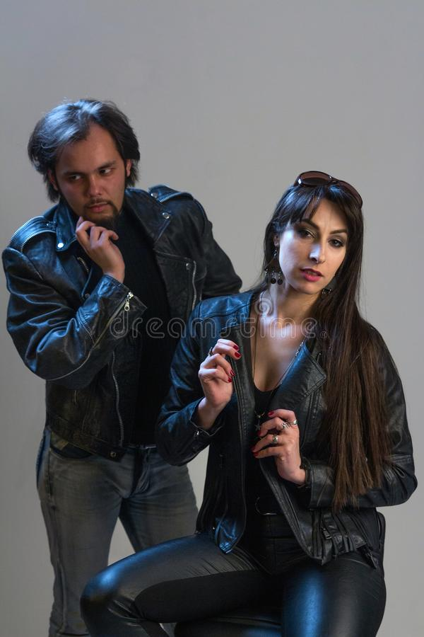 Rocker or biker style. The guy in black leather clothes is behind the girl sitting chair. Studio photosession. Modern fashionable royalty free stock image