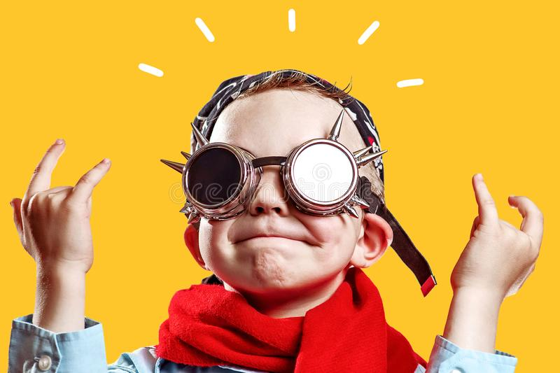 Boy in blue shirt, red scarf, biker glasses and bandana on bright background. Rocker boy in blue shirt, red scarf, biker glasses and bandana on bright background royalty free stock photography