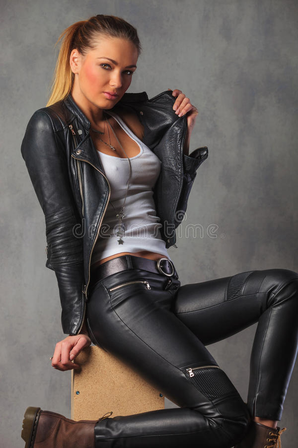 rocker girl in leather posing seated on box while fixing her jacket stock photography