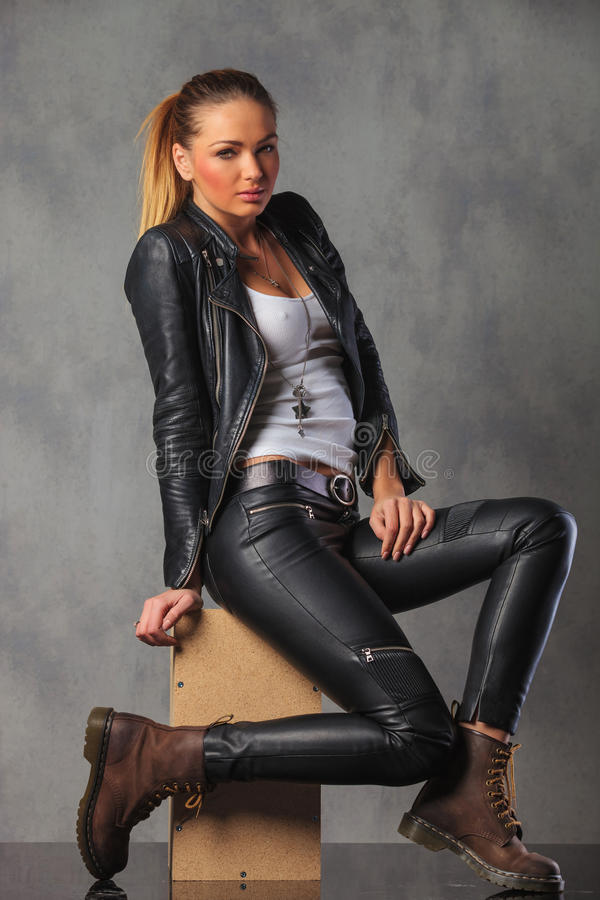 Rocker girl in leather side posing seated in studio stock photos