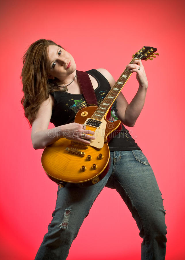 Rocker Girl Musician Electric Guitar Player. Rocker Girl Musician Guitar Player jamming on electric guitar on hot pink background stock photo
