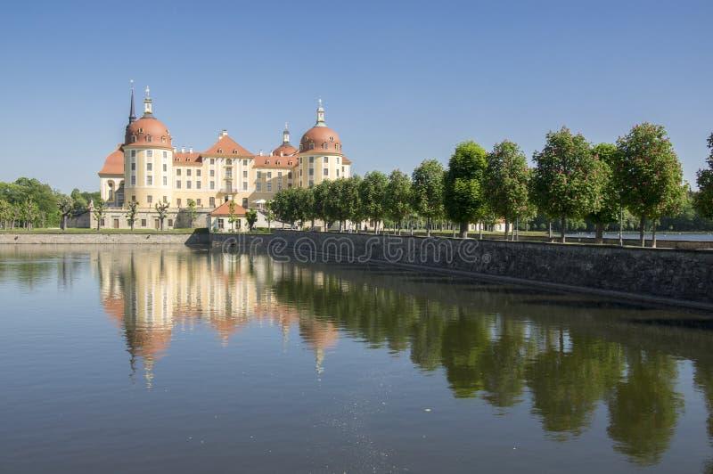 Rockera Moritzburg i Sachsen nära Dresden i Tyskland som omges av dammet, den blåa sjön för reflexionen, blå himmel royaltyfri foto