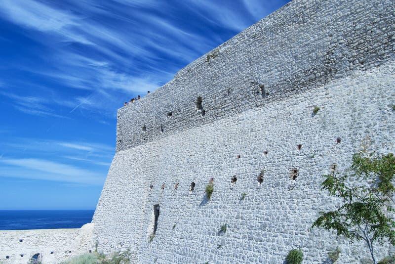 Rockera väggen i Tremiti öar med en grupp människor på överkanten som whaching seascapen för lopp- och turismbegrepp royaltyfria foton