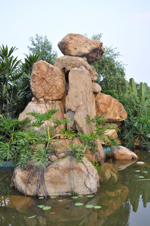 Rockery del granito in acqua dello stagno immagini stock libere da diritti