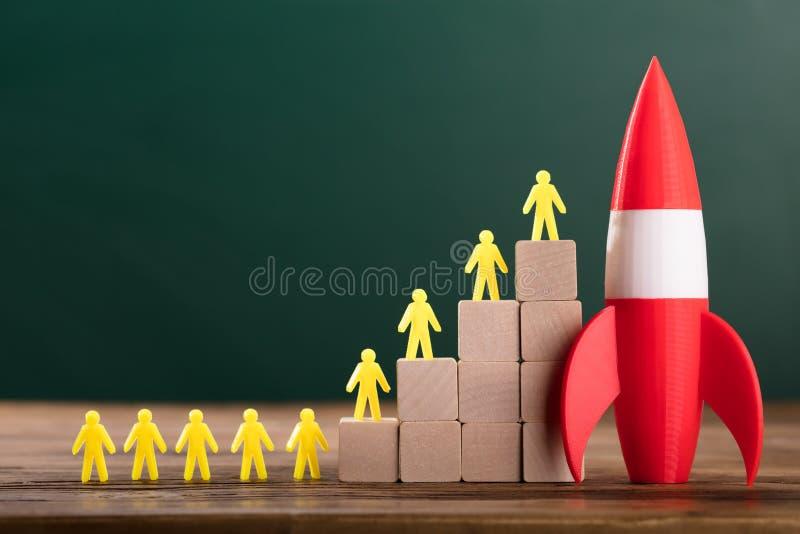 Rocket Besides Yellow Human Figures bovenop Houten Blokken royalty-vrije stock afbeelding