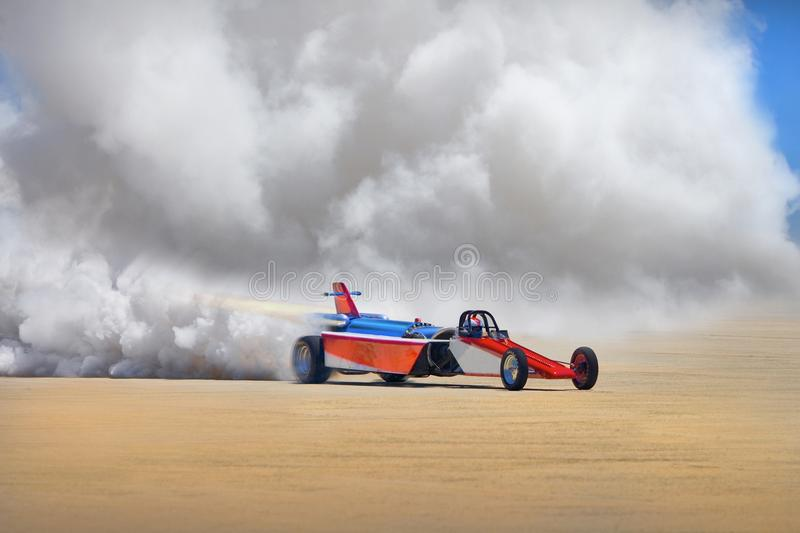 ROCKET RACE CAR AND DRIVER WITH JET PROPULSION AND HEAVY SMOKE ON TARMAC royalty free stock photos