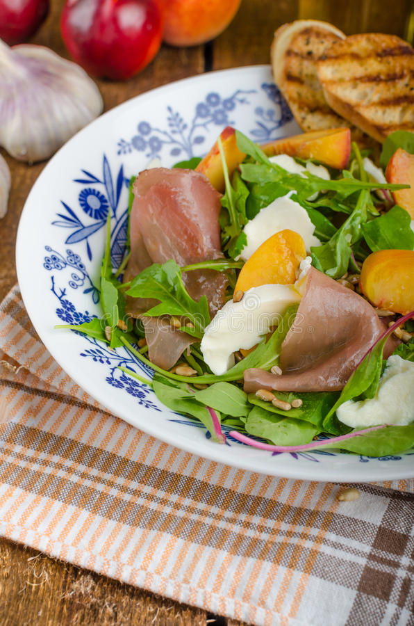Rocket salad with prosciutto and fruit. Rocket salad with prosciutto, mozzarella and peaches, panini baguette with bio garlic royalty free stock photos