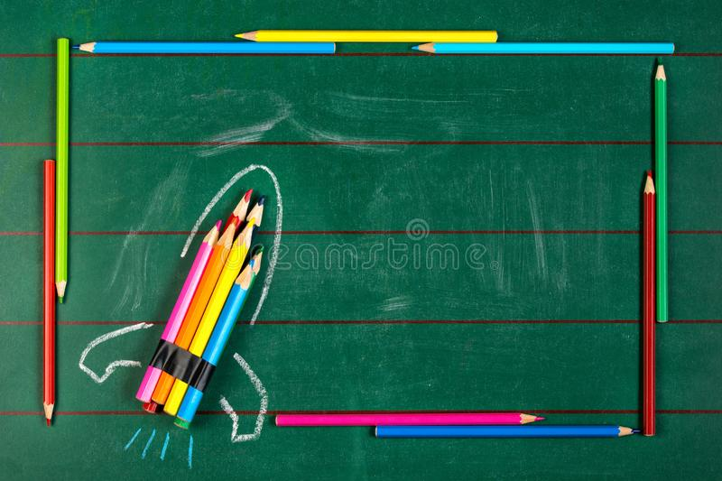 Rocket ship made of pencils on the chalkboard with pencils frame. Rocket ship made of different pencils on the chalkboard with pencils frame, back to school stock photo