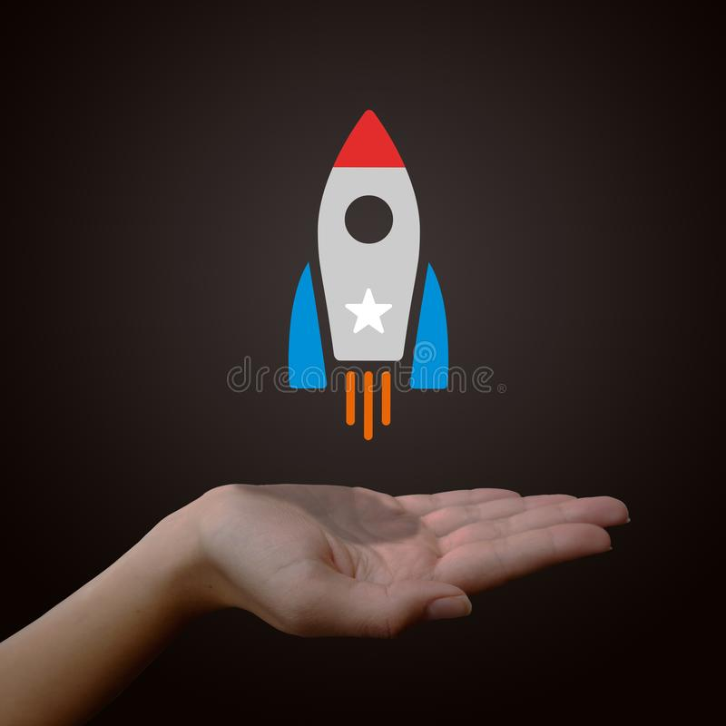 Rocket ship over female hand. Illustrated rocket ship blasting off above the open palm of a woman's hand, isolated on a black background royalty free stock image