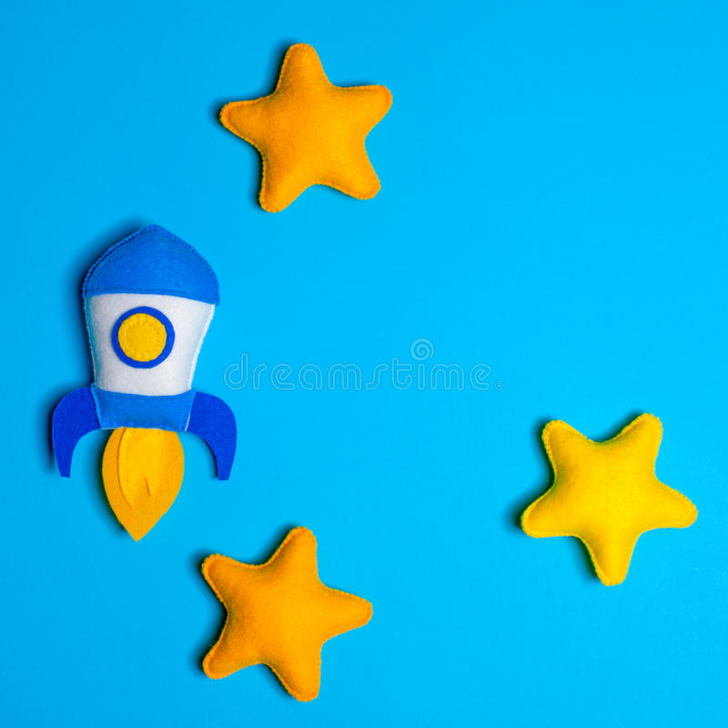 Rocket takes off. Hand made felt toys. Space ship with yellow stars on lue background. Concept for new business project start-up, increase, development, launch stock image