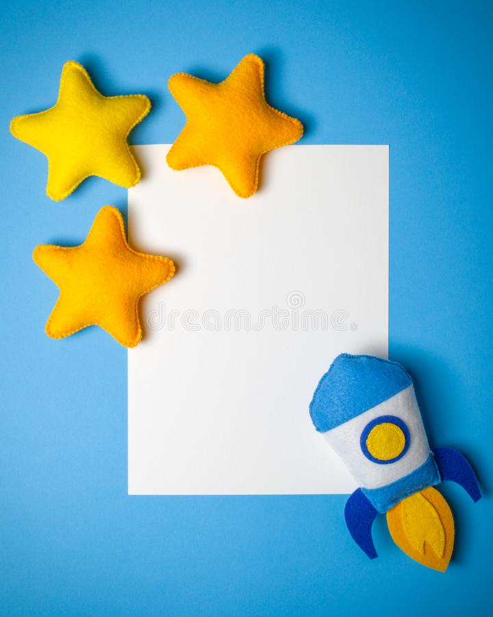 Rocket takes off. Hand made felt toys. Space ship with yellow stars on lue background. Rocket takes off. Space ship with yellow stars on lue background. Hand stock image