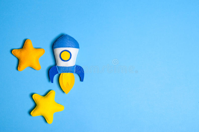 Rocket takes off. Hand made felt toys. Space ship with yellow stars on lue background. Rocket takes off. Space ship with yellow stars on lue background. Hand stock images