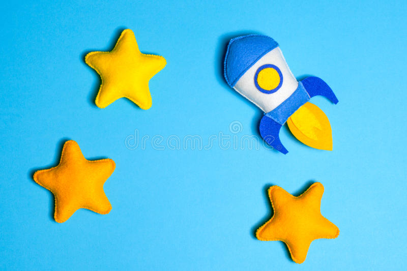 Rocket takes off. Hand made felt toys. Space ship with yellow stars on blue background. Rocket takes off. Space ship with yellow stars on blue background. Hand royalty free stock photos
