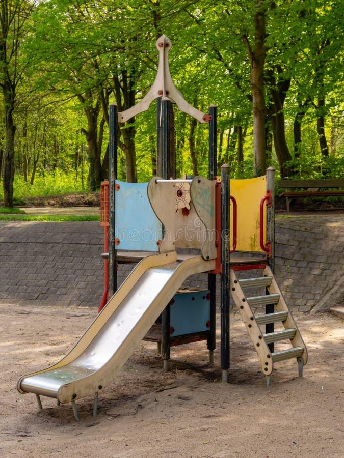 Rocketlike projetou a corrediça para crianças no campo de jogos com terra arenosa imagens de stock