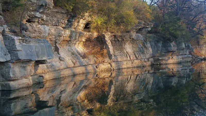 Rockface che riflette sulle acque calme immagine stock