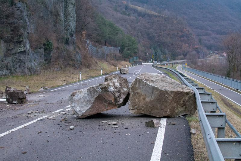 Big boulders all over the road. Rockfall on the mainroad in dolomites area, northern Italy.  Big boalder on the road. danger zone royalty free stock images