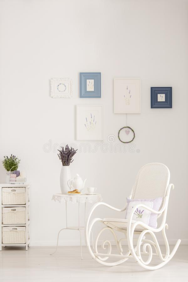 Rocking chair next to table with lavender flowers in white living room interior with posters. Real photo. Concept stock photos