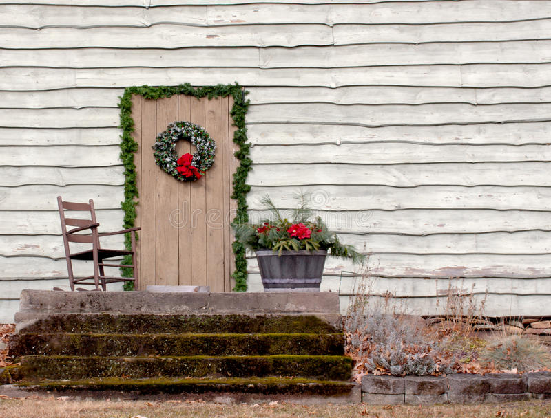 Rocking Chair On Porch. A wooden rocking chair on a porch outside a Christmas decorated house royalty free stock image