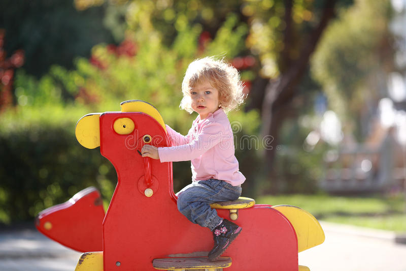 Rocking horse. Cute little girl on playground royalty free stock photography